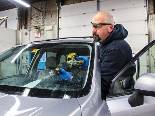 Matt Marra, an automotive technician, cuts the windshield out of a car at Portland Glass in South Burlington on Tuesday, December 6, 2016.