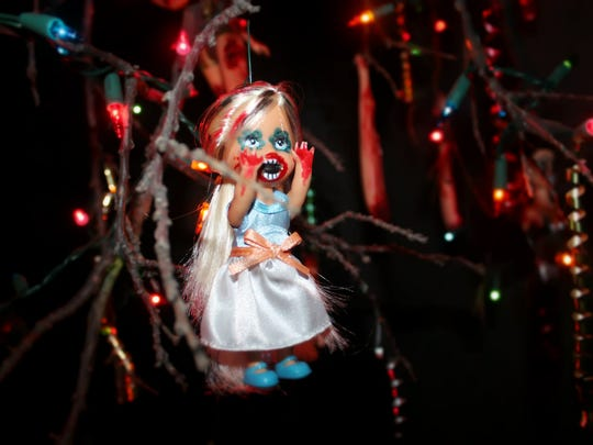 A doll mobile lit by Christmas lights hangs in one of the haunt's hallways.