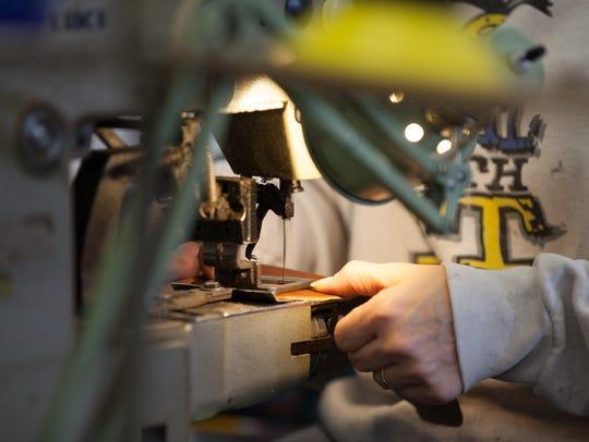 Linda Bloczynski sews the Thorogood logo onto pieces