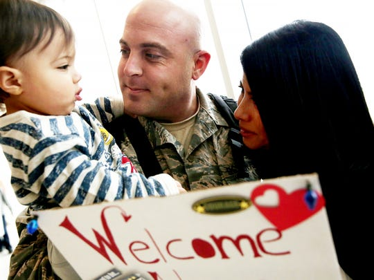Tech Sergeant Chris Dyer reunites with his wife Edi and son Landon, 14 mos., after arriving at Southwest Florida International Airport after being deployed for a year on Saturday, Dec. 17, 2016.