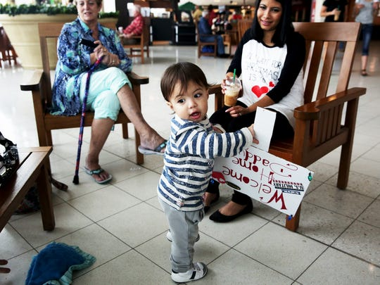 Landon Dyer, 14 mos., waits for his father Tech Sergeant Chris Dyer to arrive at Southwest Florida International Airport after being deployed for a year on Saturday, Dec. 17, 2016.