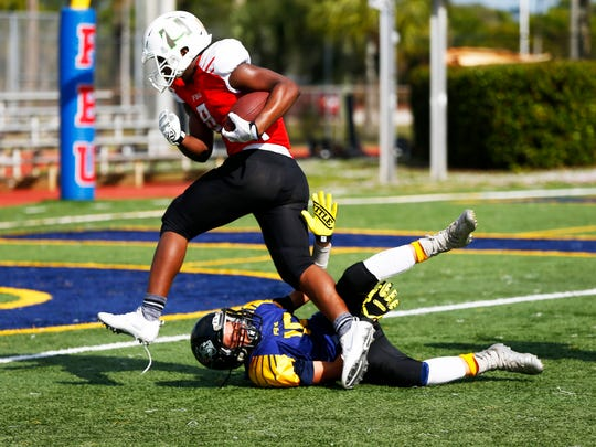 Broward County Emile Aime jumps over Illinois Darius Ragland for a touchdown during the 8th grade quarterfinal game of the Football University (FBU) National Championships at Naples High School on Saturday, Dec. 17, 2016. Broward County won with a final score of 51-0.