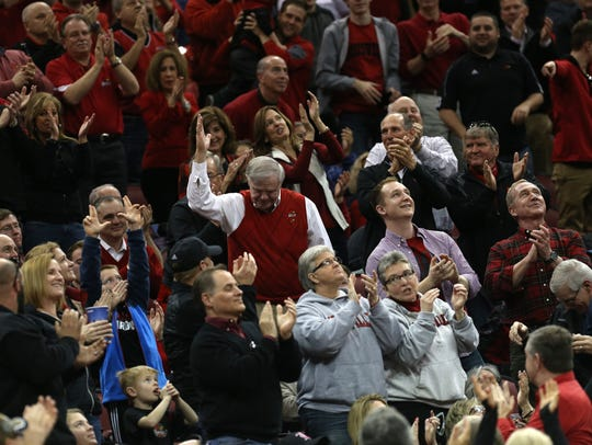 Denny Crum waves to the crowd during a 2017 Louisville basketball game at the KFC Yum Center.