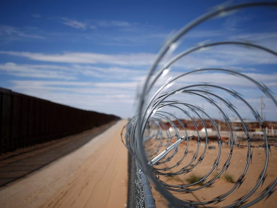 A concertina barbed wire fence stands next to a border