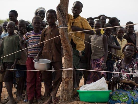 People wait in line for food at the Bidi Bidi refugee
