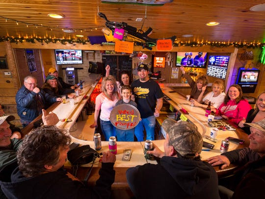 Cheri Redig, owner of Chili Corners Bar & Grill, left, her son Alik Martin, center, and husband Jeremy Martin, right, celebrate being named the No. 1 fish fry in a Marshfield News-Herald survey along with bartender Angela Verch, back, friends and family on March 30, 2017, at the bar.