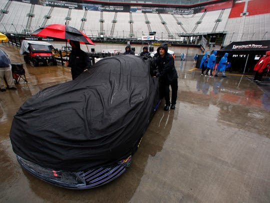 A crew team pushes a car through the pit area before for a NASCAR Monster Energy NASCAR Cup Series auto race, Sunday, April 23, 2017, in Bristol, Tenn. (AP Photo/Wade Payne)