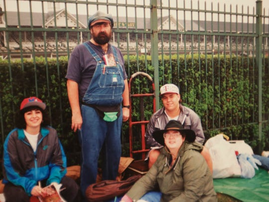 """A photograph of Russell Strange, center, at the 1994 Kentucky Derby. Strange is known for wearing his overalls and a hat that he currently can't find. """"My wife is always trying to throw it away,"""" Strange said of the missing head piece."""