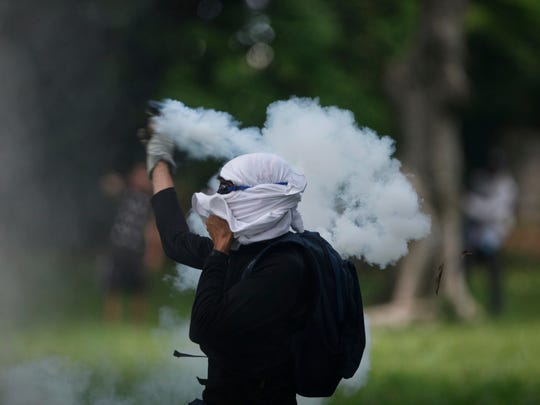 A student returns a tear gas canister fired by National Police at student protesters outside the Central University of Venezuela in Caracas, Thursday, May 4, 2017. Students held demonstrations across Caracas Thursday as a two-month-old protest movement that shows no signs of letting up claimed more lives. (AP Photo/Fernando Llano)