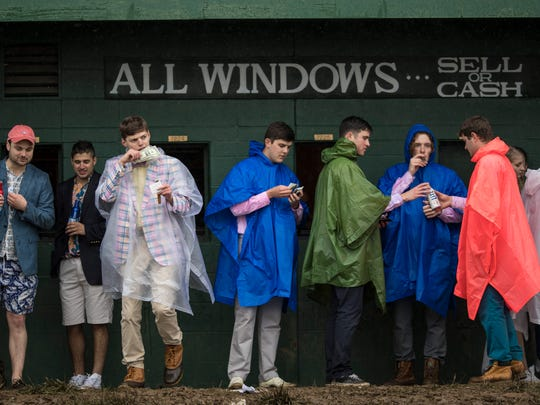 Infield attendees seek cover under a betting window awning from the rain during the Kentucky Oaks at Churchill Downs. May 5, 2017