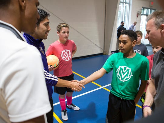 The de Paul School's Charles Mitchell, right, shakes hands with Louisville City FC soccer players during a team visit to lead a soccer practice. May 11, 2017