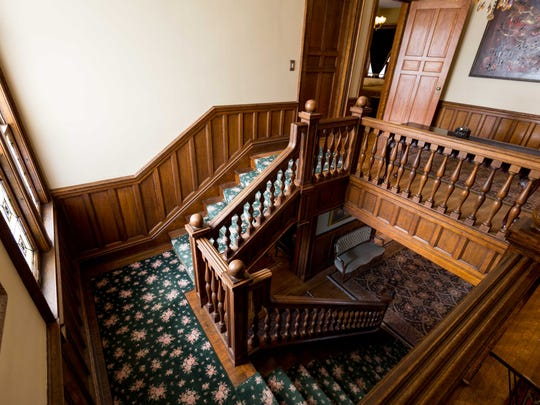 The wooden staircase rises to the bedrooms on the second