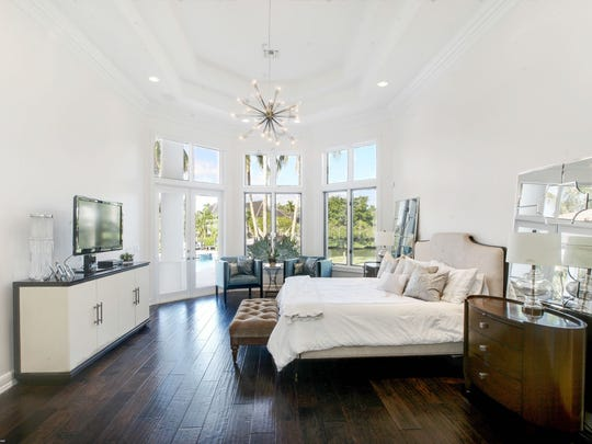The large master suite offers a sitting area with beautiful views of the pool and waterway.