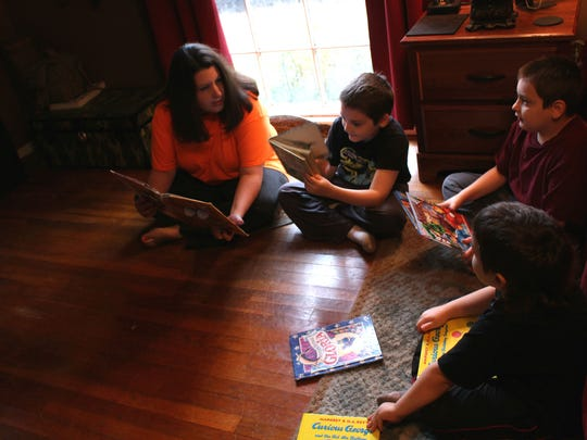 JenAlise Englade reads with three of her sons. From