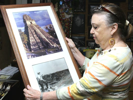 Marilyn Barham holds a framed photo of Mayan ruins