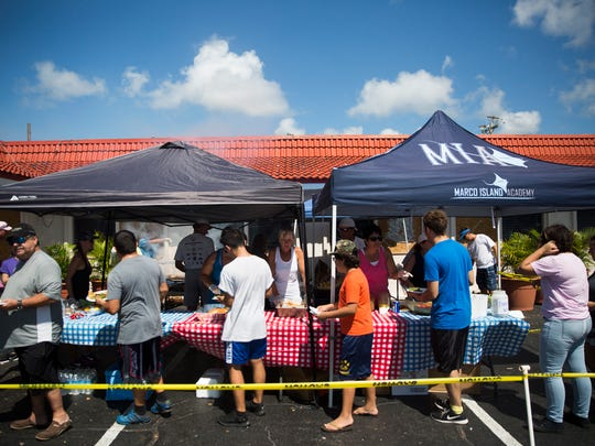 Residents line up for a meal at Kretch's on Tuesday, September 12, 2017, two days after Hurricane Irma. Kretch's and CJ's teamed up to fire up the grills to feed hot meals to those without power.