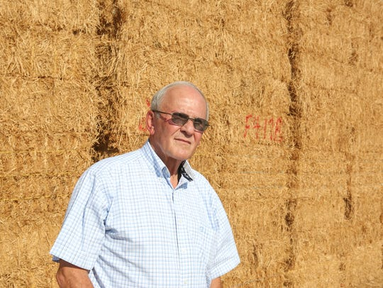 Standing beside hay bales on his farm, Palo Verde Irrigation District board member Bart Fisher talks about the agency's lawsuit against the Metropolitan Water District.