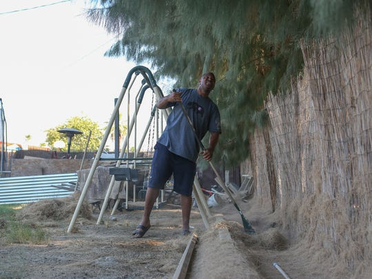 Christopher Williams rakes the needles of the tamarisk trees that dominate the backyards of the homes on Lawrence St. in Palm Springs.  The trees also form a physical barrier between the Crossley Tracts neighborhood and the Tahquitz Creek Golf Course.