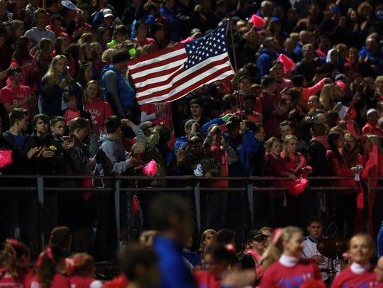 Clear Creek Amana students wave an American flag before