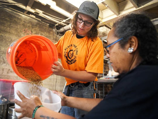 Kay Mague pours grain into a mill with help from Tina