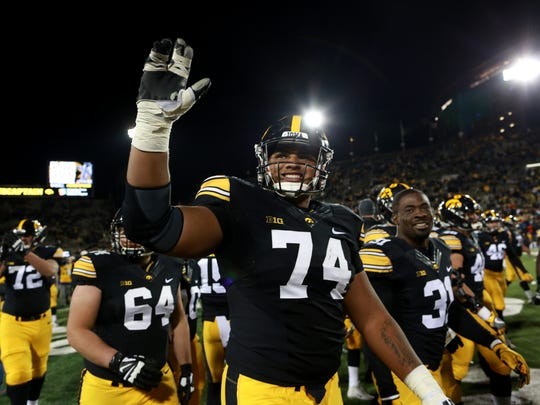 Iowa's Tristan Wirfs waves to fans following the Hawkeyes' 17-10 win over Minnesota at Kinnick Stadium on Saturday, Oct. 28, 2017.