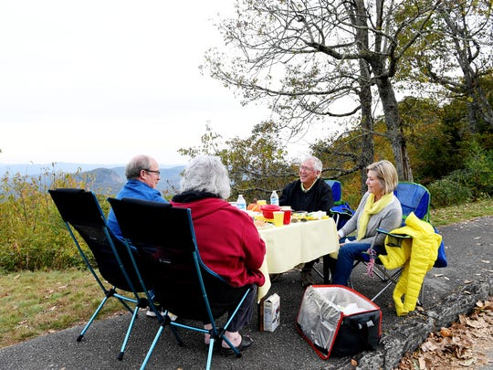From left, Kathy and Don Haehnel and John and Louise Stroup, all of Brevard, enjoy dinner with a view of Looking Glass Rock October 21, 2017. They set up at the location yearly to watch the monarch butterfly migration.