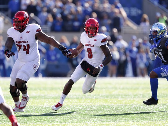 Louisville quarterback Lamar Jackson (8) looks for running room against UK behind lineman Geron Christian (74).