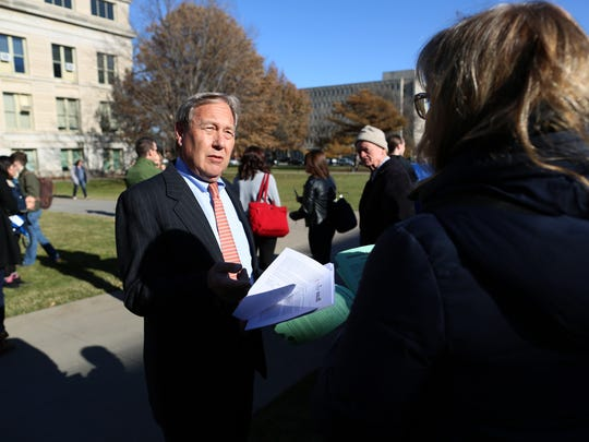 University of Iowa President Bruce Harreld gathers in support with protesters at the Pentacrest during a rally against proposed tax that would affect university graduate students on Wednesday, Nov. 29, 2017.