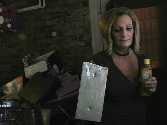 Shreveport resident Lori Grogan holds up a tool, allegedly left by a maintenance worker, that cut her after she stumbled in a dark room in her apartment. That week the light fixture had fallen out of the ceiling, Grogan said.
