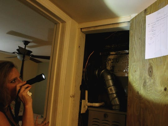 Shreveport resident Lori Grogan shines a flashlight on the air conditioning maintenance log in her apartment. Grogan is afraid to turn on the lights in her apartment for fear of starting a fire.