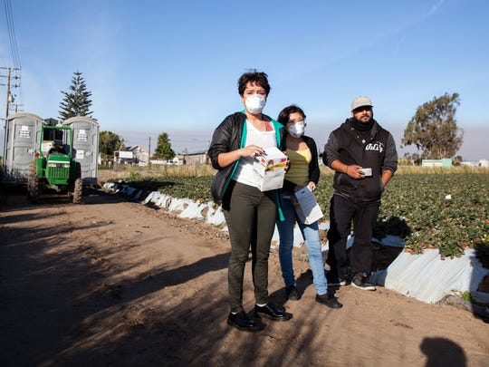 From left, Amelia Realzola, Jennifer Lopez and Raul Lopez wait for the okay to hand out N95 masks to field workers in Oxnard, California, on Friday. After originally being denied to hand out masks an unidentified man said he would hand the masks out himself.