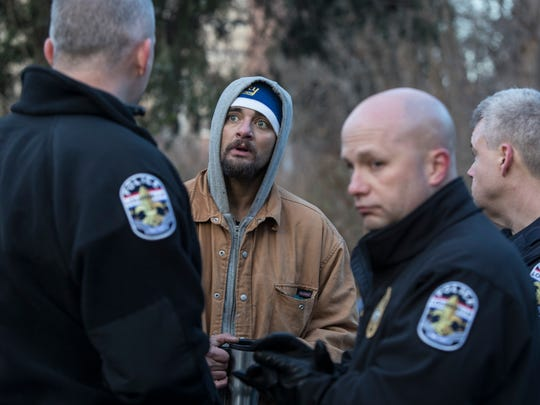 Daniel McStoots talks with Louisville Metro police officers while being removed from a homeless camp off Jefferson Street, in Louisville. Dec. 8, 2017.
