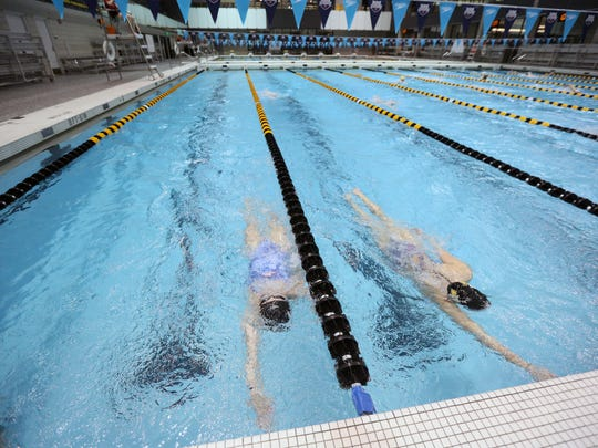 Ruby Martin, left, swims laps during practice at the