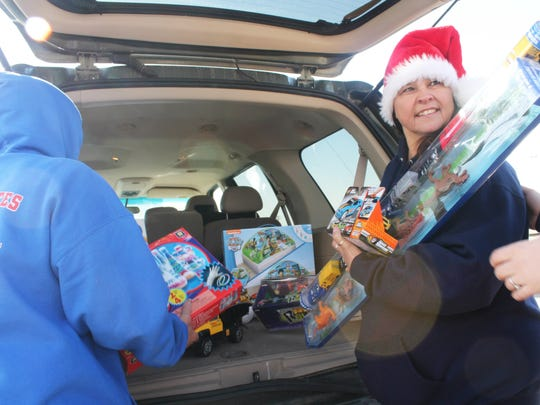 In this 2016 file photo, Nina Fierro gathers presents out of a trunk during an Alamogordo Toys for Tots collection drive at the White Sands Mall.
