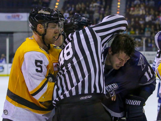 A linesman gets in between Pensacola's Charlie Adams (17) and Mississippi's Cody Walsh at the Pensacola Bay Center on Tuesday, December 26, 2017. The Ice Flyers won 2-0.