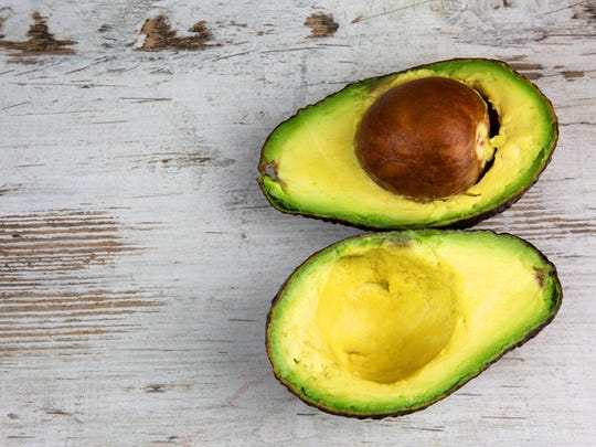 A fresh avocado cut into two halves