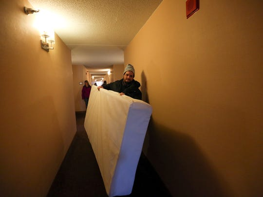 Brian Hartley takes a purchased box spring down the