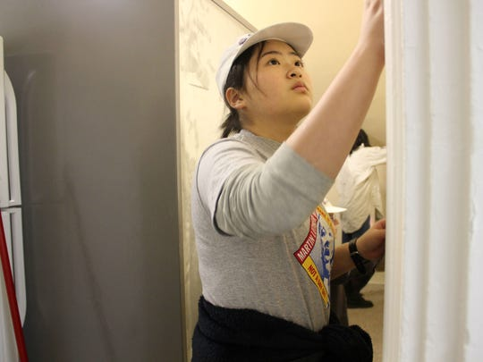 Yukiko Shimamura, 15, an exchange student from Japan, sands the walls of the Winooski Food Shelf during the MLK Day of Service in the Onion City on Monday, Jan. 15, 2018.