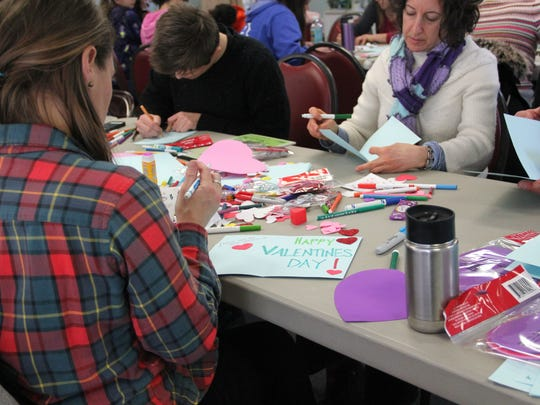 Volunteers make Valentine's Day cards for veterans and their families at the Winooski Senior Center as part of the Onion City's MLK Day of Service on Monday, Jan. 15, 2018.
