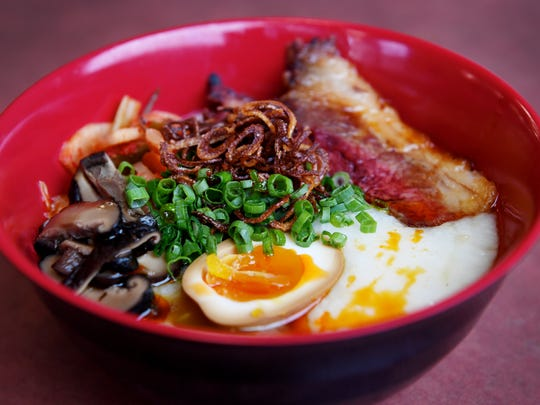 Gan Shan West's brisket congee with savory rice porridge, brisket, scallion, shiitake, kimchi, fried shallots and an egg.