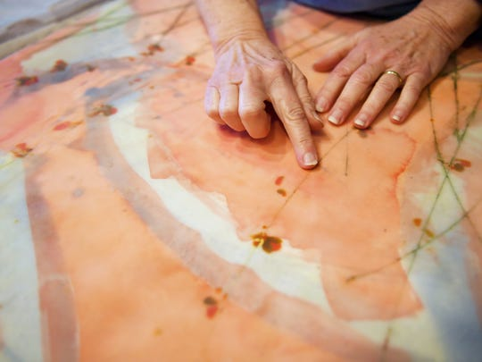 Mary Farmer touches one of her in-progress works of art after rubbing pigments into a score in the 10 layers of beeswax in her studio January 12, 2018.