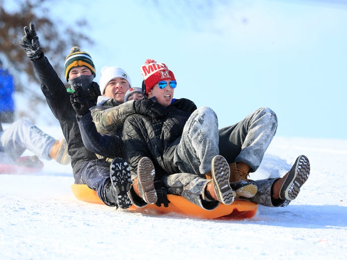 A group of boys crammed onto a single sled for a trip
