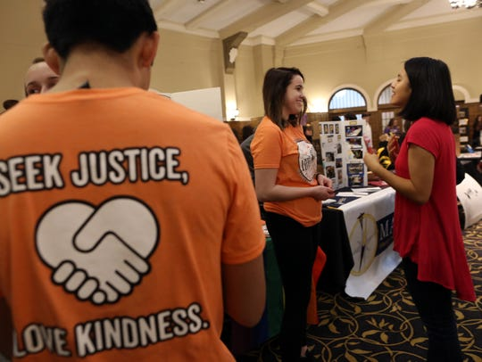 University of Iowa then-junior Abby Johnson, center, chats with a student at the Love Works booth during the student organization fair at the Iowa Memorial Union on Jan. 24, 2018.