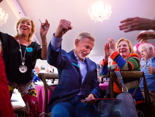 "Rick Kash, center, throws his fist in the air after winning Lot 13, ""Summertime in Paris,"" during the Naples Winter Wine Festival auction on Saturday, Jan. 27, 2018, at the The Ritz-Carlton golf resort in North Naples, Fla. Lot 13 sold for $320,000."