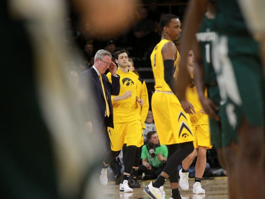 Iowa head coach Fran McCaffery brings players into