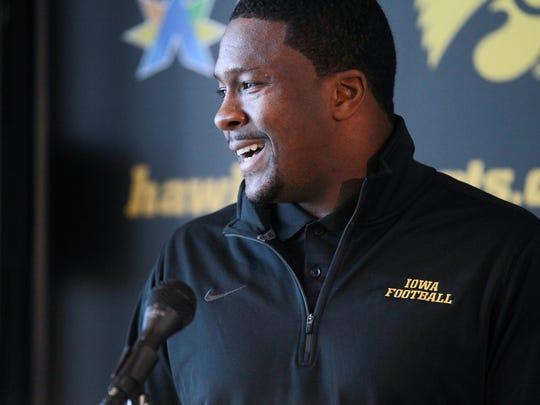 Iowa running back coach Derrick Foster greets reporters