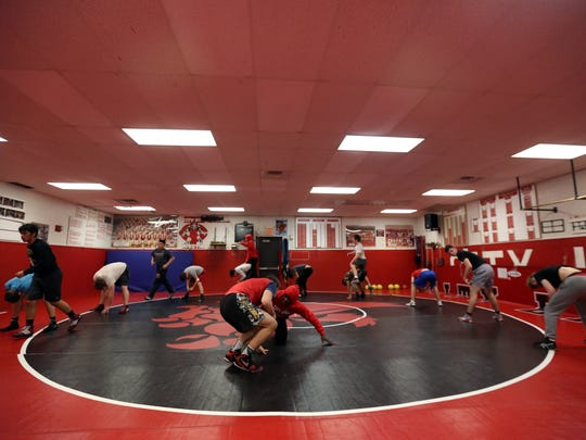 Wrestlers run warmup drills during practice on Friday,