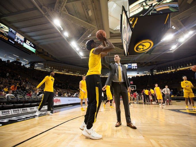 Iowa's Connor McCaffery helps Tyler Cook warm up for
