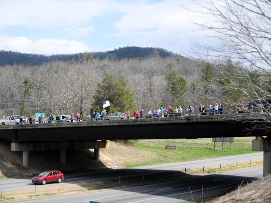 People gathered along I-40 to watch as the motorcade carrying the body of the Rev. Billy Graham heads to Charlotte February 24, 2018.