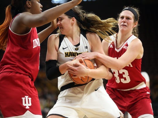 Iowa's Megan Gustafson fights off Indiana defenders during their game at Carver-Hawkeye Arena on Saturday, Feb. 24, 2018.